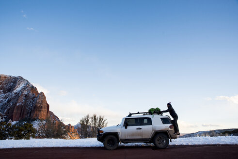 Side view of man putting backpack on off-road vehicle at desert against sky during winter - CAVF53627