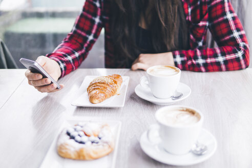 Midsection of woman with breakfast on table using mobile phone in cafe - CAVF53636