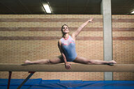 Full length of female gymnast with legs apart exercising on balance beam at gym - CAVF53648