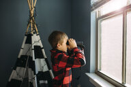 Side view of boy looking through binoculars by window at home - CAVF53663