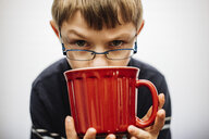 Close-up portrait of boy having drink while sitting against white background - CAVF53678