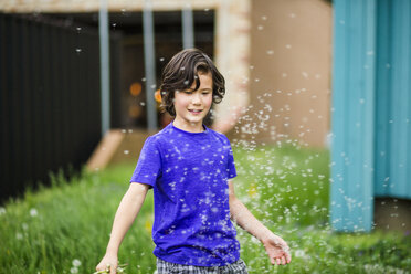 Boy playing with dandelion petals while standing at yard - CAVF53699