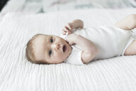 High angle view of baby girl with mouth open lying on bed at home - CAVF53705