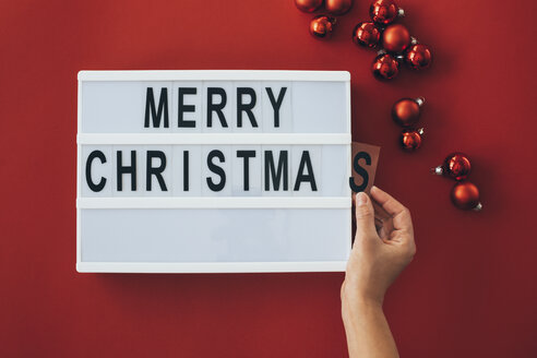 Woman's hands adding letter at 'Merry Christmas' sign - MOMF00530
