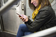 Midsection of woman using mobile phone while traveling in train - CAVF53741