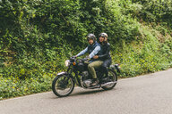 Couple riding motorcycle on road amidst trees in forest - CAVF53771