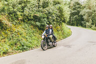 Couple riding motorcycle on road by trees and plants in forest - CAVF53774