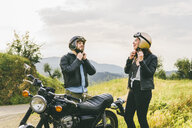 Couple wearing helmets while standing by motorcycle against sky - CAVF53777
