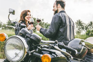 Happy couple toasting wineglasses while standing by motorcycle against sky - CAVF53783