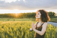 Woman meditating while standing at farm against cloudy sky during sunset - CAVF53807