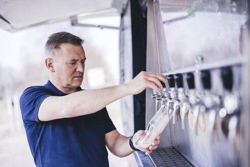 Brewer filling beer from tap while standing outdoors - CAVF53840