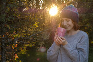 Portrait of smiling teenage girl drinking tea outdoors in autumn - LBF02165