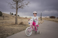 Girl looking away while riding bicycle on road against cloudy sky - CAVF53894