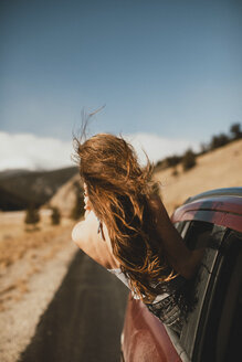 Carefree young woman with tousled hair leaning out from car window - CAVF54034