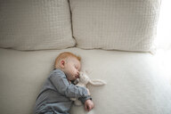High angle view of cute baby boy sleeping with stuffed toy on bed - CAVF54043