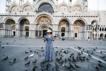 Tourist standing amidst perching birds on footpath against St Mark's Basilica - CAVF54061