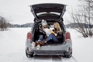Happy female friends reading map while sitting in car trunk during winter - CAVF54070