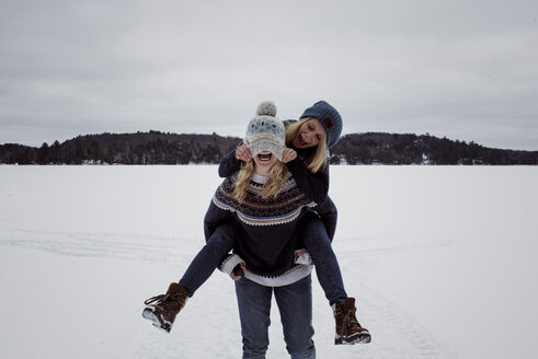 Playful woman pulling friend's knit hat while being piggybacked by her on snow during winter - CAVF54073