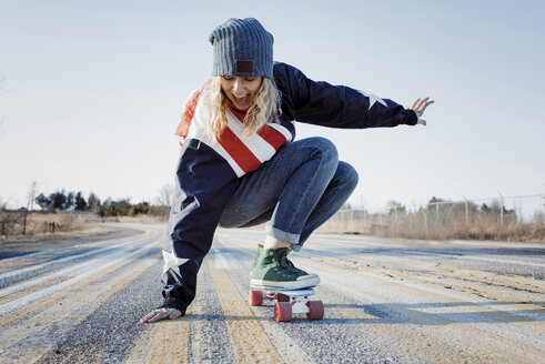 Full length of playful woman skateboarding on road during winter - CAVF54076