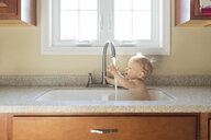 Shirtless baby boy playing with water while sitting in kitchen sink - CAVF54082