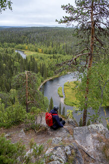 Finland, Oulanka National Park, woman with backpack sitting in pristine nature - PSIF00154