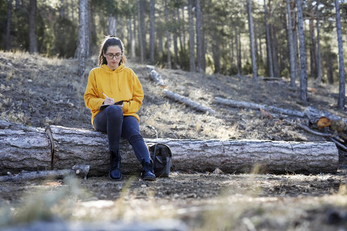 Young woman with yellow sweater in the forest, writing - GRSF00003