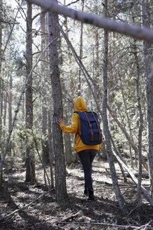 Rear view of young woman with yellow sweater and blue bag in the forest, exploring - GRSF00006