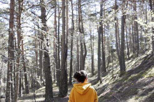 Rear view of young woman with yellow sweater in the forest - GRSF00009