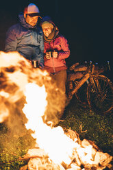 Couple with with bikes standing at camp fire looking at flame by night - OCMF00094