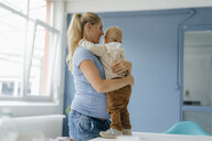 Happy pregnant mother embracing toddler son standing on table - KNSF05206