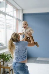 Pegnant mother lifting up happy toddler son - KNSF05221