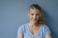 Portrait of smiling blond woman standing at blue wall - KNSF05230