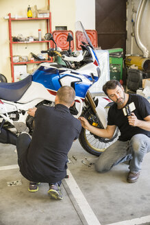 Mechanic working on motorcycle in workshop filmed by his partner - FBAF00153