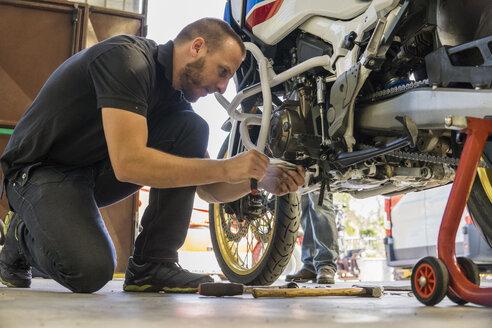 Mechanic working on motorcycle in workshop - FBAF00159