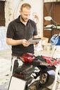 Man using tablet next to motorcycle in workshop - FBAF00165