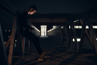 Sportive young man with smartphone and earphones standing on a bridge at night - ZEDF01734