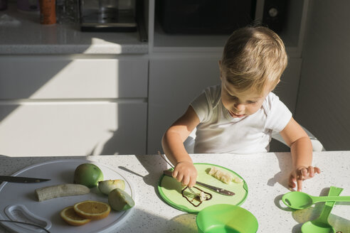 Little boy sitting at table in the kitchen eating fruits - MOMF00533