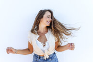 Happy young woman shaking her hair in front of white wall - KIJF02075