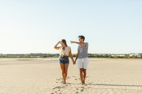 Young couple walking hand in hand on the beach - KIJF02084