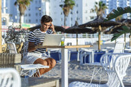 Man with laptop sitting on the terrace of a beach bar - KIJF02090