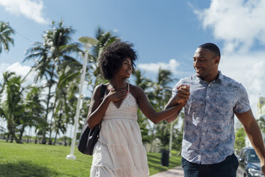 USA, Florida, Miami Beach, happy young couple walking down the road together - BOYF00780