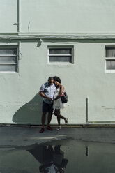 Smiling young couple standing at building at a puddle - BOYF00789