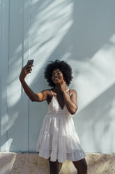 Smiling young woman wearing white dress taking a selfie at a wall - BOYF00816