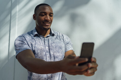 Smiling young man wearing shirt taking a selfie at a wall - BOYF00822