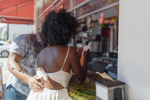 Young couple choosing from menu at a kiosk - BOYF00843