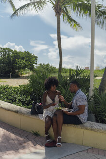 USA, Florida, Miami Beach, young couple with salad and cell phone in a park - BOYF00855