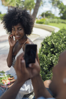 USA, Florida, Miami Beach, young man taking a picture of girlfriend eating a salad in a park - BOYF00858