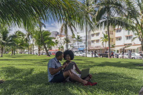 USA, Florida, Miami Beach, young couple using tablet and laptop on lawn in a park - BOYF00861