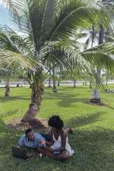 USA, Florida, Miami Beach, young couple using tablet and laptop on lawn in a park - BOYF00867