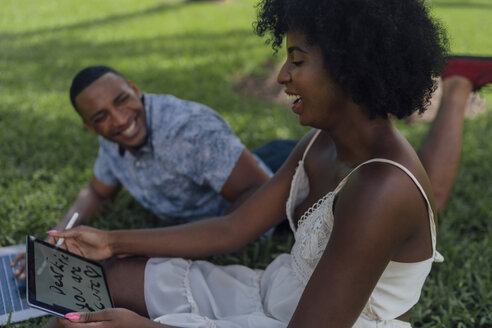 Happy young woman with boyfriend in a park using tablet - BOYF00870
